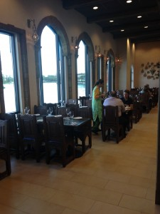 The right side of Spice Road table is an interior seating area with large windows to the lagoon