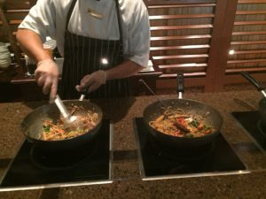 the chef mixes in your noodles and sauce, completing your Wok dish
